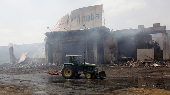 A tractor runs past a damaged building on the tarmac of Jinnah International Airport, after Sunday's attack by Taliban militants, in Karachi June 10, 2014.(Reuters / Athar Hussain )