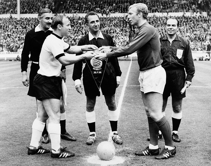 West Germany's and England's national soccer team captains, Uwe Seeler (L) and Bobby Moore, exchange pennants as Swiss referee Gottfried Dienst (C) looks on before the start of the World Cup final on 30 July 1966 at Wembley stadium in London (AFP Photo)