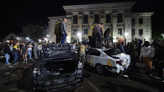 Protesters stand on top of the crashed cars during a rally against the Russian President Vladimir Putin in front of the Russian embassy in Kiev on June 14, 2014. (AFP Photo / Sergei Supinsky)