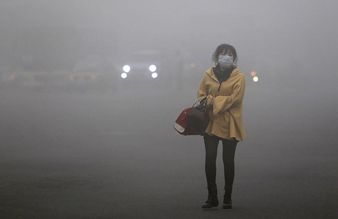 A woman wearing a face mask walks in heavy smog in Harbin, northeast China's Heilongjiang province, on October 21, 2013. (AFP Photo)