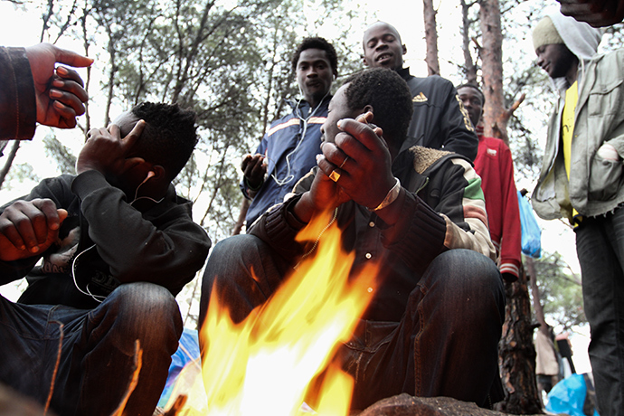 A group of Malian migrants trying to keep warm with a bonfire in the forest on the slopes of Gurugu. Photo by @TomasoClavarino