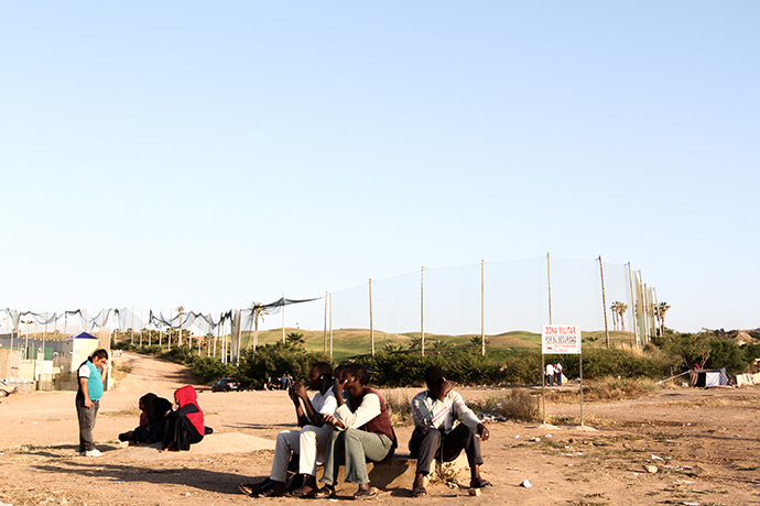 Malian migrants waiting for dinner in front of Melilla's CETI (Centro de Estancia Temporal de Inmigrantes). Photo by @TomasoClavarino