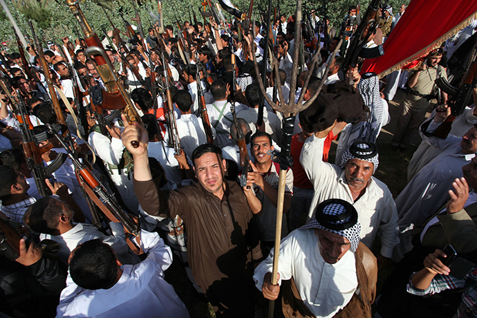 Iraqi Shiite tribesmen brandish their weapons as they gather to show their readiness to join Iraqi security forces in the fight against Jihadist militants who have taken over several northern Iraqi cities, on June 16 2014, in the southern Shiite Muslim shrine city of Najaf (AFP Photo)
