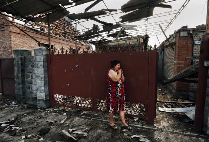 Yekaterina Len, 61, cries outside her destroyed house following what locals say was overnight shelling by Ukrainian forces in the outskirts of the eastern Ukrainian town of Slaviansk May 20, 2014. (Reuters/Yannis Behrakis)