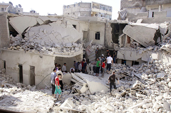 Syrian residents search the rubble for survivors following a reported air strike by government forces on June 18, 2014 in the northern city of Aleppo. (AFP Photo / Baraa Al-Halabi)