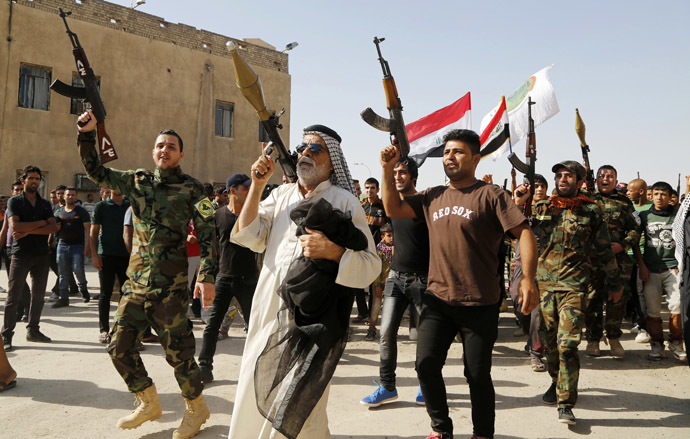 Volunteers, who have joined the Iraqi Army to fight against predominantly Sunni militants, carry weapons during a parade in the streets in Baghdad's Sadr city June 14, 2014. (Reuters/Ruben Sprich)