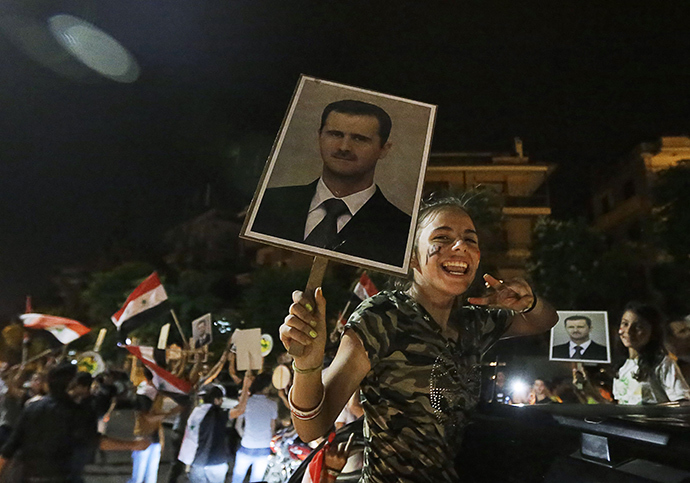 A girls gestures and holds a picture of re-elected Syrian President Bashar al-Assad as she celebrates in Damascus after Assad was announced as the winner of the country's presidential elections on June 4, 2014 (AFP Photo)