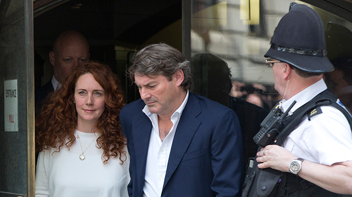 Former News International chief executive Rebekah Brooks (L) and her husband Charlie (R) leave the Old Bailey courthouse in London June 24, 2014 (Reuters / Neil Hall)