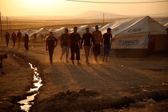 Iraqi refugees, who fled from the violence in Mosul, walk during sunset inside the Khazer refugee camp on the outskirts of Arbil, in Iraq's Kurdistan region, June 27, 2014 (Reuters / Ahmed Jadallah)