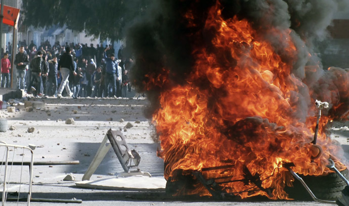 Tyres set on fire by protesters burn during clashes with police in Kasserine January 8, 2014. (Reuters)