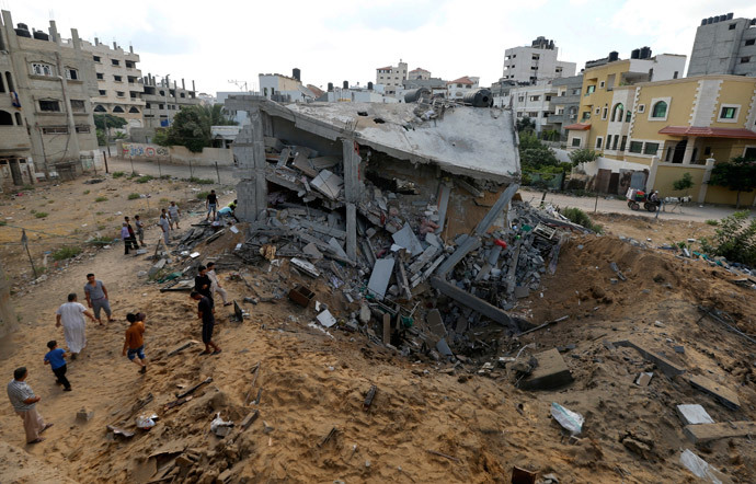Palestinians gather around the remains of a house which police said was destroyed in an Israeli air strike in Gaza City July 14, 2014.(Reuters / Mohammed Salem )