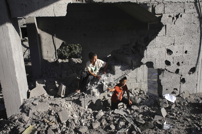 Palestinian boys are seen in a damaged house as they look at the remains of a neighboring house which police said was destroyed in an Israeli air strike in Rafah in the southern Gaza Strip July 16, 2014. (Reuters)
