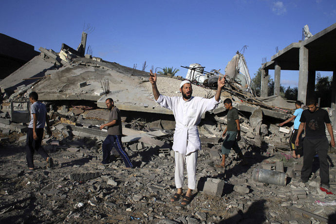 A Palestinian man gestures as he speaks to members of the media in front of a house which police said was destroyed in an Israeli air strike in Rafah in the southern Gaza Strip July 16, 2014. (Reuters)