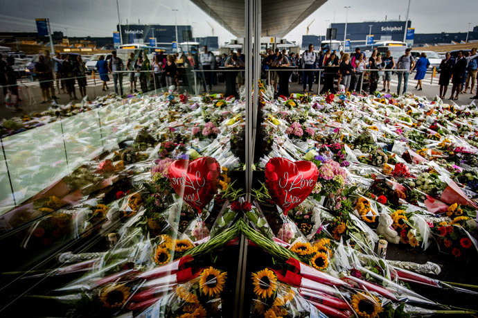People look at the flowers left in remembrance for the victims of the MH17 plane crash at Schiphol Airport, near Amsterdam, on July 21, 2014 (AFP Photo / ANP / Robyn Van Lonkhuijsen Netherlands out)