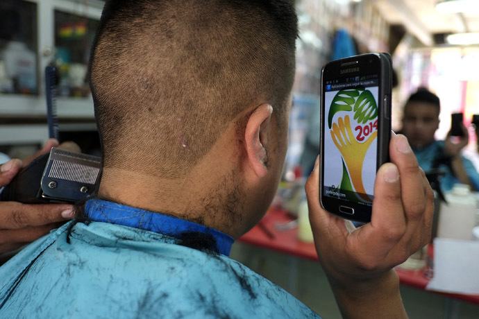 A soccer fan holds up his mobile phone showing the 2014 World Cup logo, which he is getting shaved on his head, at a hairdresser in La Paz, July 7, 2014. (Reuters/David Mercado)