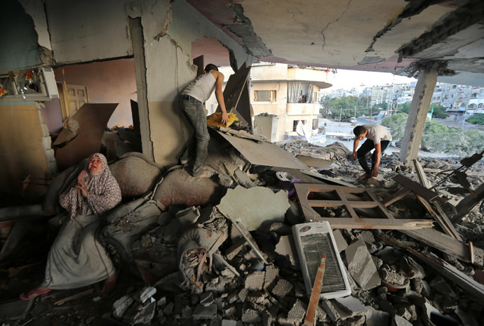 A Palestinian woman (L) cries inside her damaged house, which police said was targeted in an Israeli air strike, in Gaza City July 17, 2014. (Reuters/Mohammed Salem)