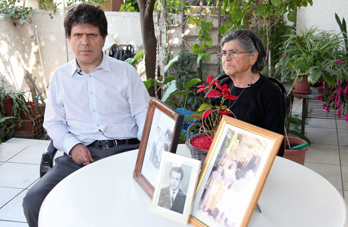 Greek Cypriot Marios Kouloumas poses near his mother, on February 14, 2014 in Nicosia, with pictures of his father who is one of hundreds of Greek and Turkish Cypriots who disappeared during a decade of unrest culminating in the Turkish invasion of 1974. (AFP Photo / Barbara Laborde)