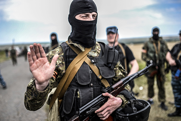 An armed member of self-defense forces gestures as he blocks the way to the crash site of Malaysia Airlines Flight MH17, near the village of Grabove, in the region of Donetsk on July 20, 2014. (AFP Photo / Bulent Kilic)