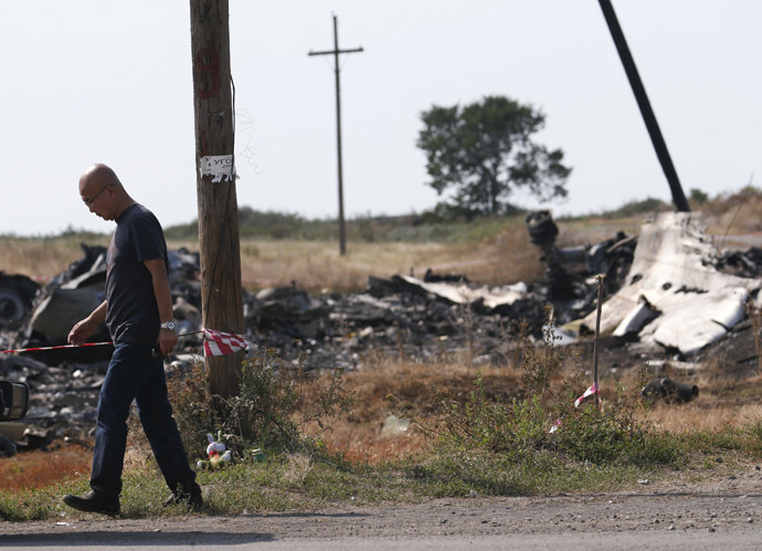 A Malaysian air crash investigator works at a crash site of the Malaysia Airlines Flight MH17 near the village of Hrabove (Grabovo), Donetsk region July 24, 2014. (Reuters/Maxim Zmeyev)