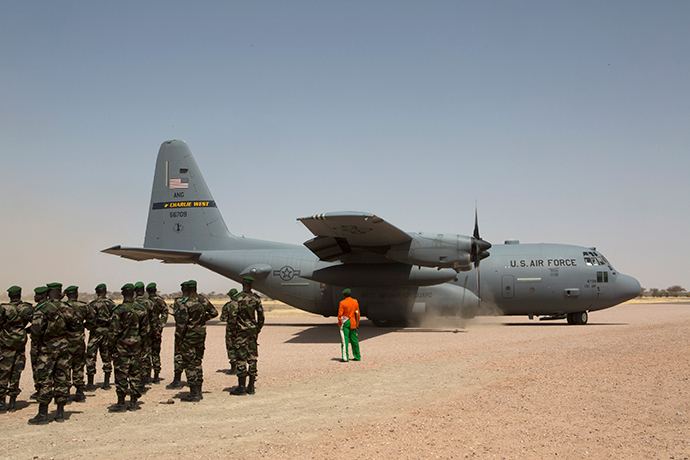 A C-130 U.S. Air Force plane lands as Nigerien soldiers stand in formation during the Flintlock military exercise in Diffa, March 8, 2014 (Reuters / Joe Penney)