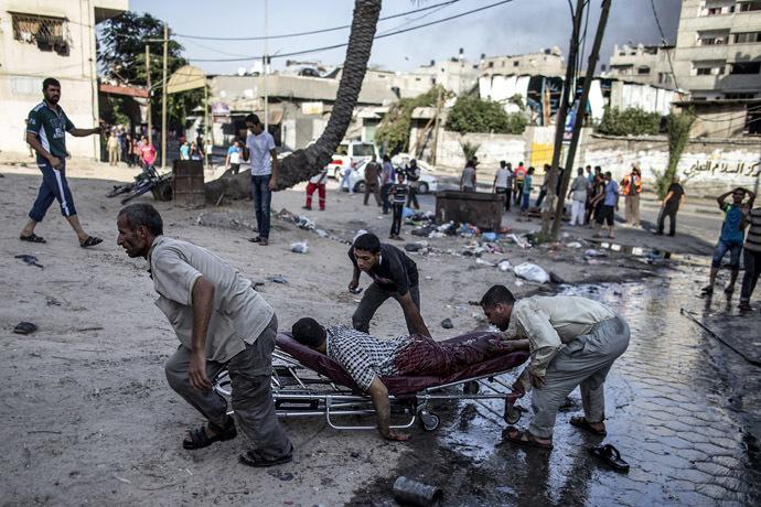 Palestinian men move the victim of an Israeli air strike on a market place to an ambulance in the Shejaiya neighbourhood near Gaza City on July 30, 2014. (AFP Photo)