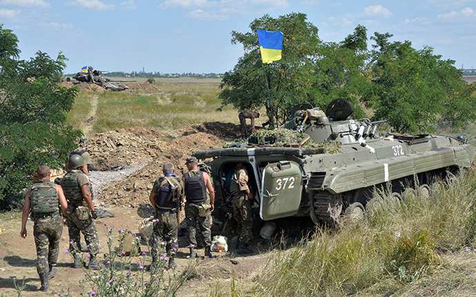 Ukrainian servicemen stand next to an armoured vehicle topped with a Ukrainian flag as they take up a position near the eastern city of Debaltceve, in the region of Donetsk (AFP Photo / Genya Savilov)