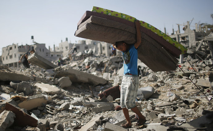 A Palestinian carries mattresses from his destroyed house in the Shejaia neighborhood, which witnesses said was heavily hit by Israeli shelling and air strikes during Israeli offensive, in the east of Gaza City August 1, 2014. (Reuters)