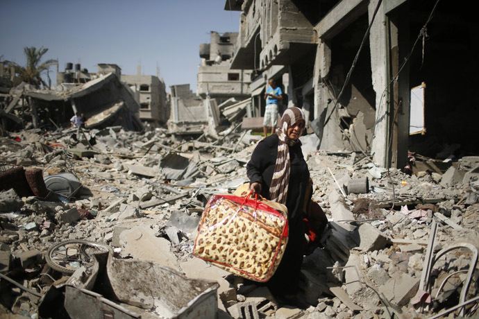 A Palestinian woman carries her belongings from her destroyed house in the Shejaia neighborhood, which witnesses said was heavily hit by Israeli shelling and air strikes during an Israeli offensive, in the east of Gaza City August 1, 2014. (Reuters/Mohammed Salem)