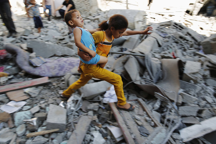 A Palestinian girl carries a child across rubble from a building that police said was destroyed by an Israeli air strike, in the Burij refugee camp in the central Gaza Strip August 1, 2014. (Reuters/Finbarr O'Reilly)