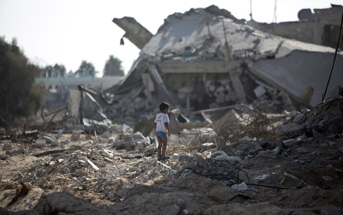 A Palestinian boy walks over debris as civilians who were displaced from their houses due to fighting between Israel's army and Hamas fighters return to check their homes in Gaza City's Shejaiya neighbourhood, on August 1, 2014. (AFP Photo)