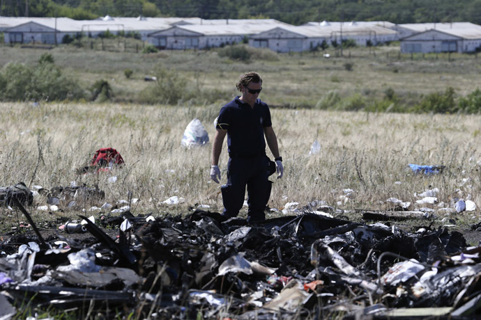 A member of a group of international experts inspects the site where the downed Malaysia Airlines flight MH17 crashed, near the village of Hrabove (Grabovo) in Donetsk region, eastern Ukraine August 1, 2014. (Reuters)