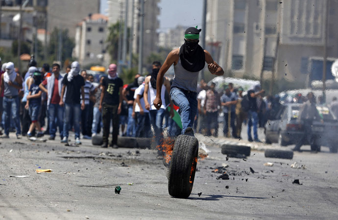 A Palestinian protester kicks a burning tyre during clashes with Israeli troops at a protest against the Israeli offensive in Gaza, outside Israel's Ofer military prison near the West Bank city of Ramallah August 1, 2014 (Reuters)