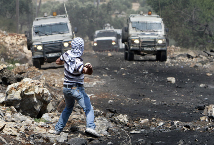 A Palestinian protester throws stones toward Israeli troops during clashes following a protest against the nearby Jewish settlement of Qadomem, in the West Bank village of Kofr Qadom near Nablus May 16, 2014. (Reuters)