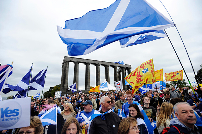 Pro-independence supporters wave the Saltire as they gather in Edinburgh on September 21, 2013 for a march and rally in support of a yes vote in the Scottish Referendum to be held in September 2014 (AFP Photo / Andy Buchanan)