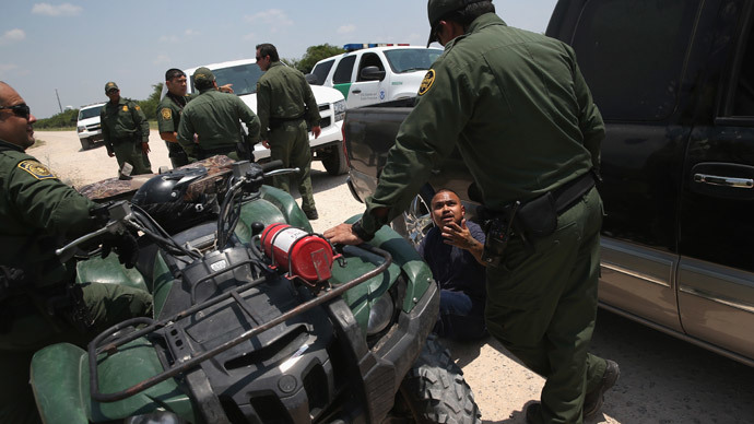 Border Patrol agents detain a suspected smuggler after he allegedly transported undocumented immigrants who crossed the Rio Grande from Mexico into the United States on July 24, 2014 in Mission, Texas.(AFP Photo / John Moore)