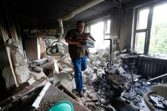A man inspects wreckage inside a damaged building following what locals say was shelling by Ukrainian forces in Donetsk August 7, 2014. (Reuters / Sergei Karpukhin)