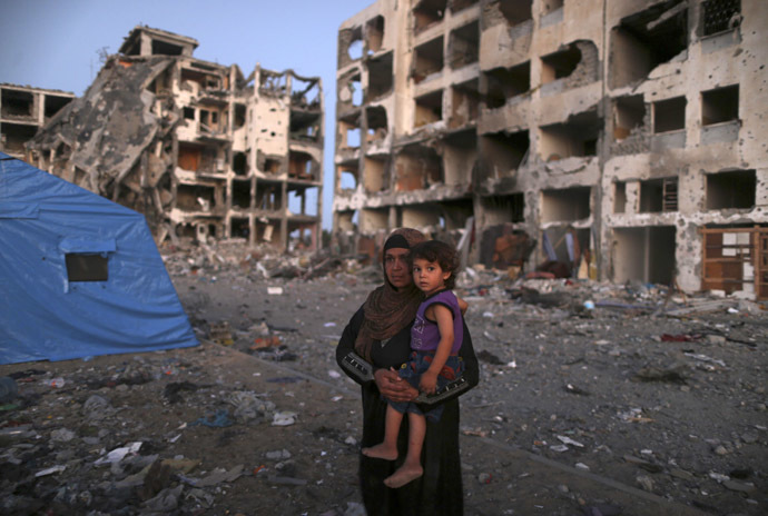 A Palestinian woman carries her daughter as she leaves her house near the remains of residential buildings in Beit Lahiya town, which witnesses said was heavily hit by Israeli shelling and air strikes during the Israeli offensive, in the northern Gaza Strip August 7, 2014. (Reuters)