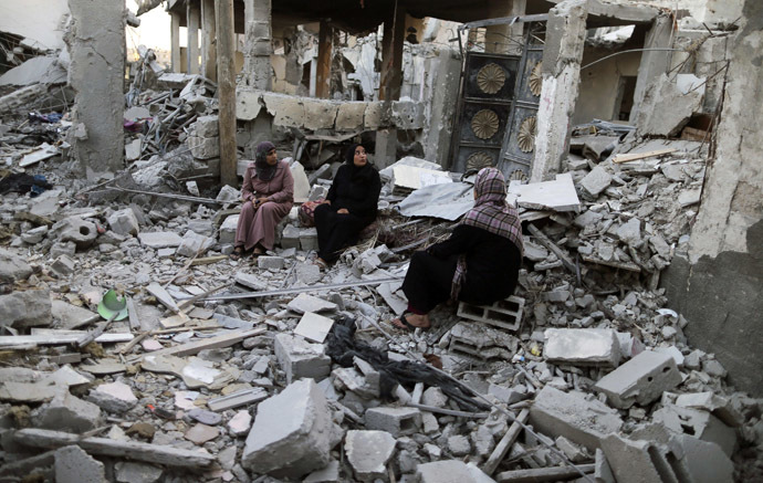 Palestinians sit outside their destroyed house in Beit Hanoun town, which witnesses said was heavily hit by Israeli shelling and air strikes during the Israeli offensive, in the northern Gaza Strip August 7, 2014. (Reuters)
