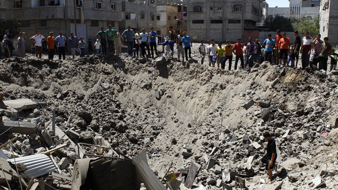 People look at a crater on the ground and damaged buildings, that witnesses said was caused by an Israeli air strike, in the Zeitoun neighbourhood in Gaza City August 8, 2014. (Reuters)
