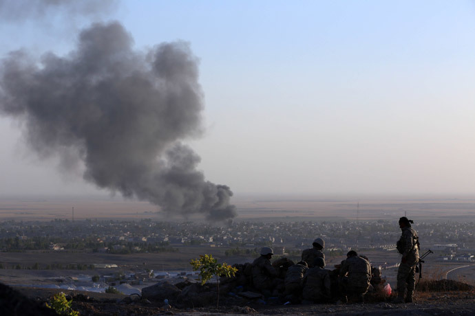 Iraqi Kurdish Peshmerga fighters look on as smoke billows from the town Makhmur, about 280 kilometres (175 miles) north of the capital Baghdad, during clashes with Islamic State (IS) militants on August 9, 2014. (AFP Photo / Safin Hamed)