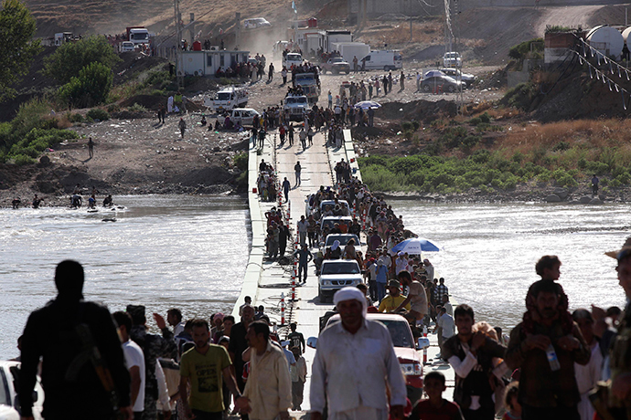 Displaced people from the minority Yazidi sect, fleeing the violence in the Iraqi town of Sinjar, re-enter Iraq from Syria at the Iraqi-Syrian border crossing in Fishkhabour, Dohuk province, August 10, 2014 (Reuters / Ari Jalal)