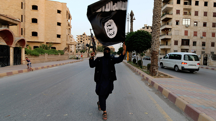 A member loyal to the Islamic State in Iraq and the Levant (ISIL) waves an ISIL flag in Raqqa June 29, 2014 (Reuters / Stringer)
