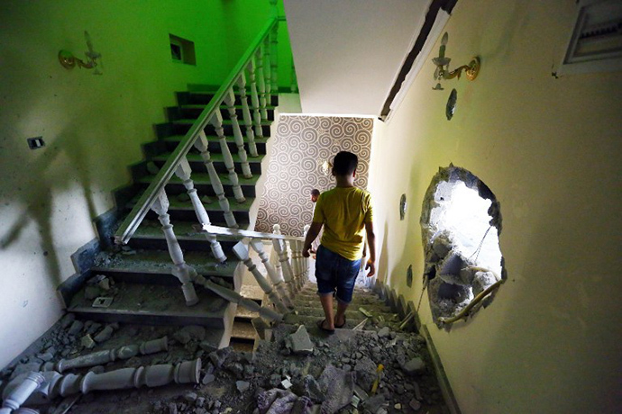 A youth walks down the stairs near a hole in the wall of a house at a former Libyan army camp known as Camp 27, in the Libyan capital Tripoli, on August 11, 2014 following reported clashes between rival militias. (AFP Photo / Mahmud Turkia)