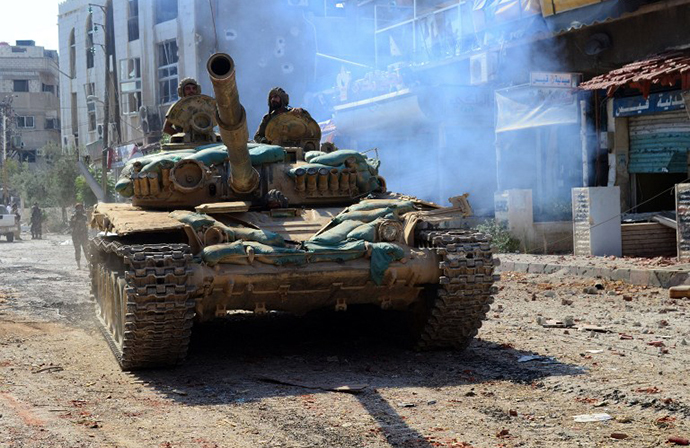 A handout picture released by the official Syrian Arab News Agency (SANA) on August 14, 2014, shows a Syrian army tank advancing in a street in Mleiha on the outskirts of the capital Damascus. (AFP Photo / SANA)