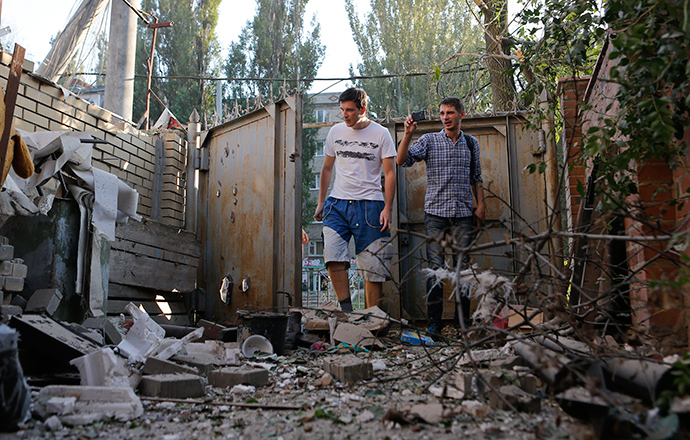 People walk in front of a building damaged by, what locals say, was recent shelling by Ukrainian forces in Donetsk August 20, 2014 (Reuters / Maxim Shemetov)