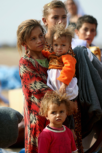 Displaced people from the minority Yazidi sect, who fled the violence in the Iraqi town of Sinjar, wait to board a bus to re-enter Iraq from Syria, at Nowruz refugee camp in Qamishli, northeastern Syria, August 17, 2014 (Reuters / Rodi Said)