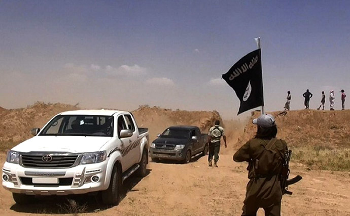 An image made available by the jihadist Twitter account Al-Baraka news on June 11, 2014 allegedly shows a militant of the jihadist group Islamic State of Iraq and the Levant (ISIL) waving the Islamic Jihad flag as vehicles drive on a newly cut road through the Syrian-Iraqi border between the Iraqi Nineveh province and the Syrian town of Al-Hasakah. (AFP Photo)