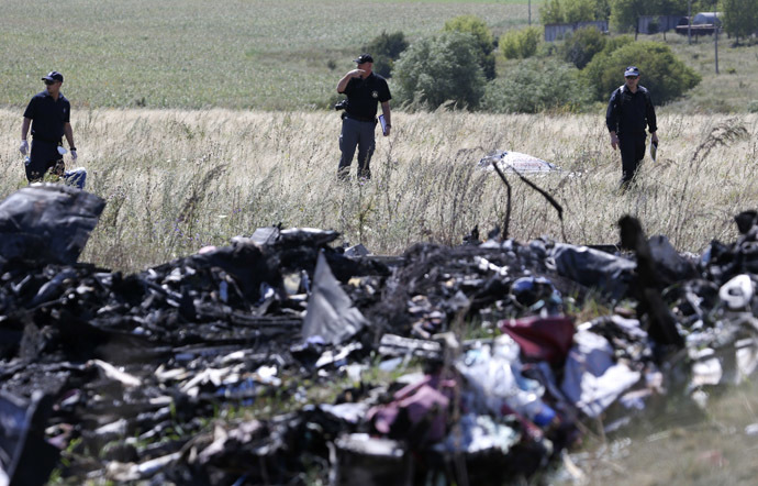 A group of international experts, including members of the Dutch police mission, work at the site where the downed Malaysia Airlines flight MH17 crashed, near the village of Hrabove (Grabovo) in Donetsk region, eastern Ukraine August 1, 2014. (Reuters/Sergei Karpukhin)