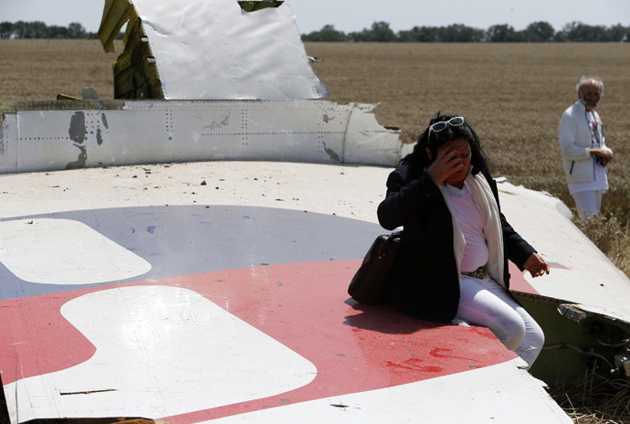 Angela Dyczynski sits on a piece of wreckage of Malaysia Airlines Flight MH17 near her husband Geaorge (R) during their visit to the crash site near the village of Hrabove (Grabovo), Donetsk region July 26, 2014. According to local media, Perth-based Dyczynski's daughter Fatima was aboard the Malaysia Airlines plane en route from Amsterdam to Kuala Lumpur when it was brought down in eastern Ukraine on July 17. (Reuters/Sergei Karpukhin)