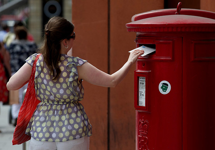 A woman posts a letter in a Royal Mail post box in London (AFP Photo / Andrew Cowie)